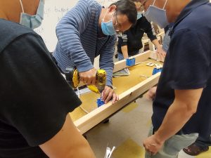 job development class using drill to fix lights and lightbulbs